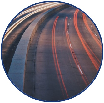 """Picture of a highway with streaked red and white colors from vehicle brake and headlights, respectively. The picture symbolizes a wide variety of transportation research areas: safety, congestion mitigation, transportation infrastructure, etc. It is a logo for the research theme of: """"Addressing Region 6 Transportation Needs""""."""