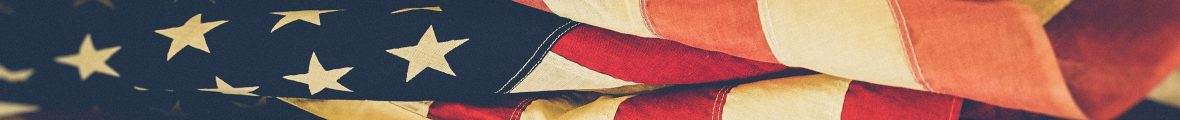 Horizontal banner comprised of an image of an unfurled American flag.